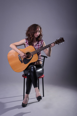 soloist: Young woman plays on an acoustic guitar, isolated on a gray background. A woman in leather pants and a shirt sits on a chair and holds a guitar.