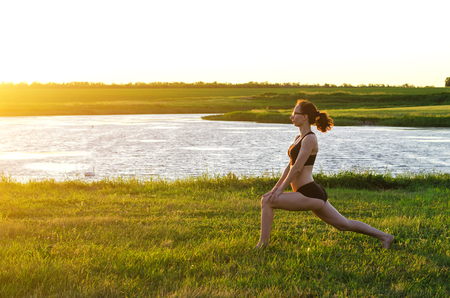 A sports woman performs exercises at sunset, a copy of the free space. A young woman in top and shorts practicing yoga on the shore of the lake.