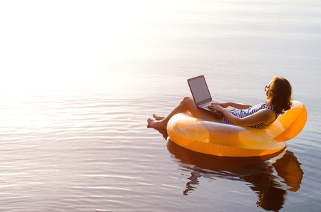 Business woman working on a laptop in an inflatable ring in the water, a copy of the free space. Workaholic, work on vacation.