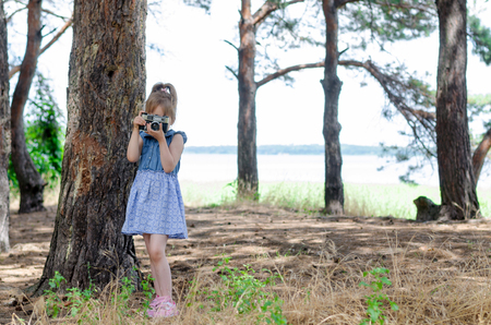 A little girl with a retro camera takes pictures in the forest, a copy of the free space. A small photographer, a rest and a hobby.