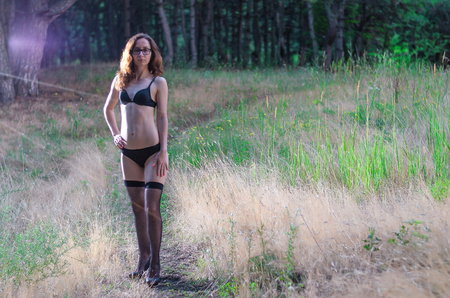 A young woman in lingerie and stockings is standing in the forest, a copy of the free space. 免版税图像