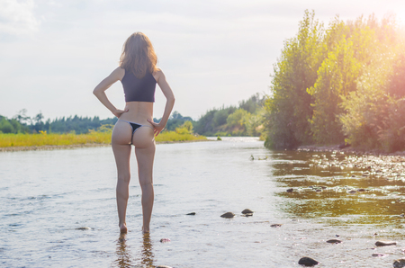 Young woman in the river, free spaces. A woman in a bikini enters the river, a view from behind.