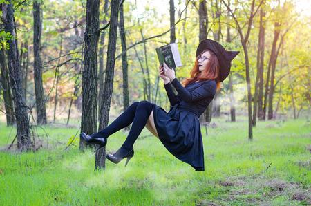 Levitação: a bruxa lê um livro pendurado no chão, um feriado de Halloween. Mulher em uma fantasia de bruxa, carnaval.