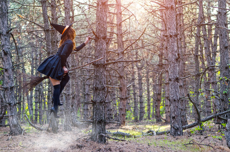 Levitation, a witch in a hat flies on a broom, free space. Halloween holiday, magic. Stock Photo