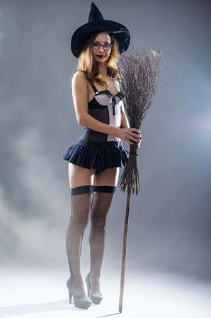 Achtergrond van Halloween, jonge vrouw in een heksenkostuum, vrije ruimte. Een vrouw in een carnavalskostuum met een bezem.
