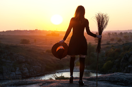Woman in a witch costume with a broom and hat, a background of halloween. The witch looks at the sunset, free space. Stock Photo