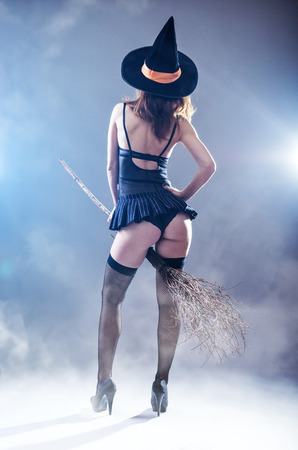 gray: Background to Halloween, sexy woman in a witch costume with a broom, view from the back. Young woman in a carnival costume of a witch on a gray background.