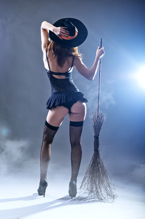 Background to Halloween, sexy woman in a witch costume with a broom, view from the back. Young woman in a carnival costume of a witch on a gray background.