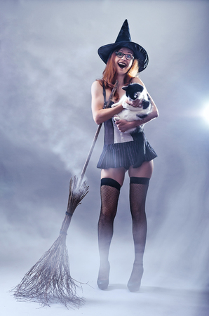 Woman in witch costume holding a cat, photos in the smoke. Sexy woman in a carnival costume and a broom on a gray background.