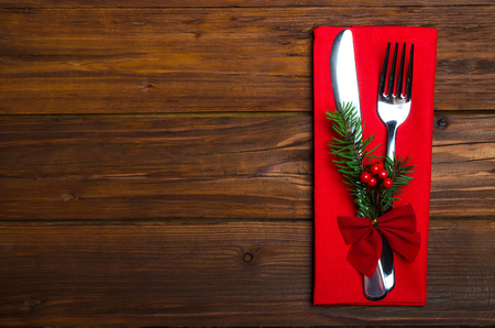 Christmas table: knife and fork, napkin and Christmas tree branch on a wooden table top view with copy space. New Years decor of the festive table.