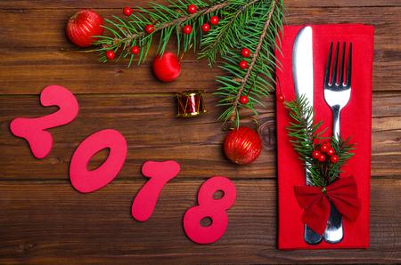 Feestelijke tafel met een vork, mes, servet en vuren tak van bovenaf. Nieuwjaarsdecoratie en inschrijving 2018.