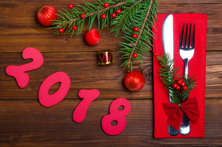 Festive table with a fork, knife, napkin and spruce branch from above. New Year decor and inscription 2018.