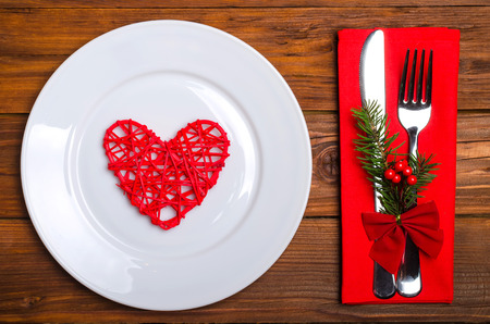 Christmas table: knife and fork, plate, napkin and Christmas tree branch on a wooden table top view with copy space. New Years decor of the festive table.