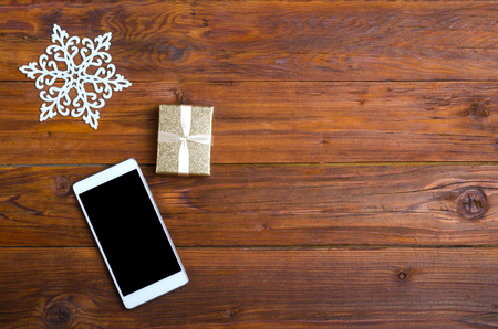 Christmas background: smartphone, and a gift on a wooden table top view with copy space. Banner for advertising. Stock Photo