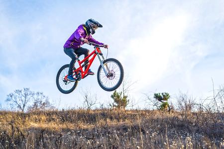 ? yclist está saltando desde un trampolín alto, el cielo y el espacio libre para su texto. Deportes extremos, ciclista de montaña, mtb.