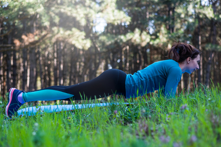 Young woman doing plank outdoors. Active way of life, free expression. Beautiful girl engaged in fitness in the park, sports figure, sportswoman, exercise bar.