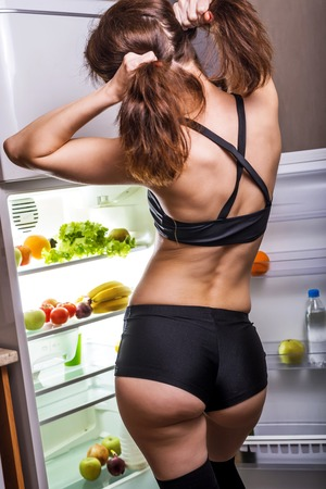 Sexy young woman in sports shorts geting food from the fridge. Slender woman looking in the fridge, rear view. Foto de archivo