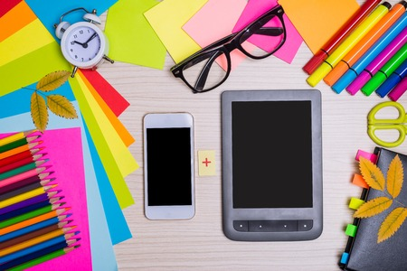 Stationery on the wooden desk from above. Bright pencils, colored paper and gadgets: a smartphone and an e-book on the school desk. Stock Photo