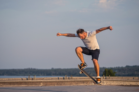 Skateboarder doing an ollie trick on background of blue sky. Active lifestyle.