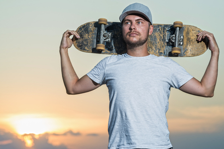 Portrait of a stylish skateboarder in the background of a bright sunset. Active lifestyle.