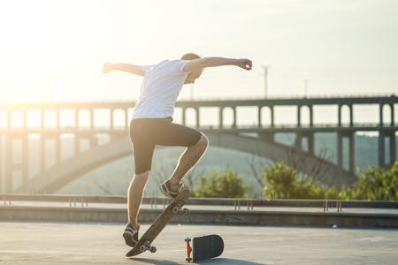 Skateboarder doing a trick in a jump at sunset. Active lifestyle. Reklamní fotografie