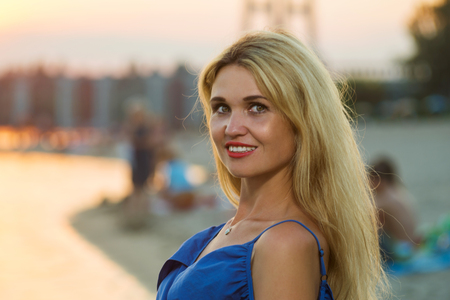 Stylish young woman with long hair, free space. Beautiful girl near the river.