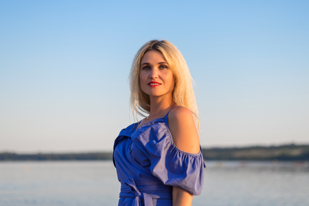 Beautiful young woman on the river bank. Stylish woman with long hair. Stok Fotoğraf