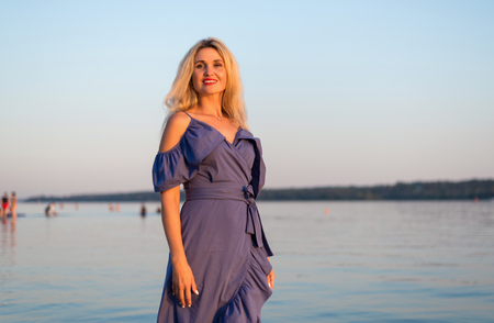Stylish young woman with long hair on the river bank, free space. Beautiful girl in a dress on the beach.