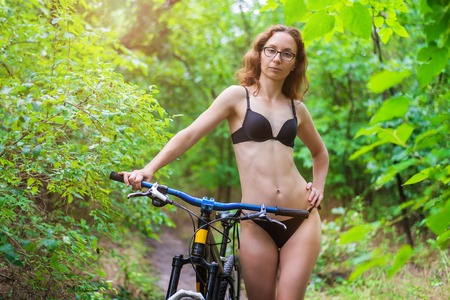 Slender woman posing near the bike in the forest.
