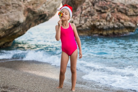 Cute girl in santa claus hat and lollipop on the beach, free space. Christmas background. Winter holidays in tropical countries.