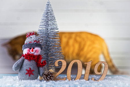 New Year's composition: snowman, inscription 2019 and Christmas tree on a wooden background. Christmas background with copy space.
