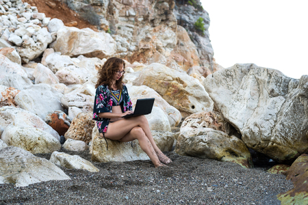 Business woman working on a laptop while sitting on a rock on the beach. Remote work, freelance.