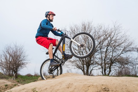 Man on a mountain bike performs a dirty jump. Active lifestyle, mtb.