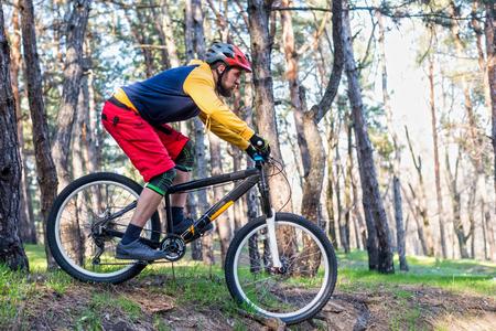Ciclismo, un ciclista in abiti luminosi in sella a una mountain bike attraverso i boschi. Stile di vita attivo, competizione enduro.