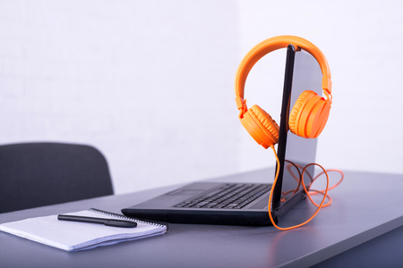 Laptop on the office desk. Workplace: laptop, orange headphones, a notebook and pen. Standard-Bild - 121482197