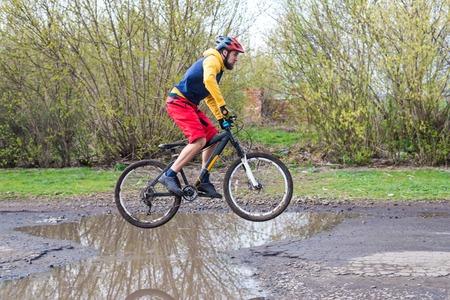 Ein Radfahrer in roten Shorts und gelber Jacke, der auf dem Hinterrad durch eine Pfütze fährt. Aktives Leben an der frischen Luft.