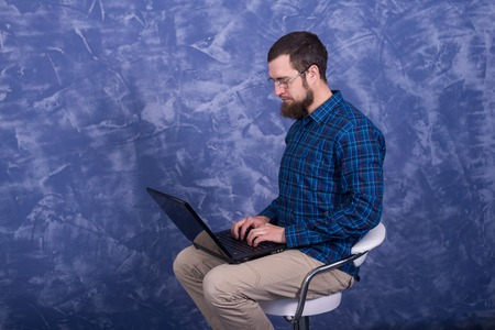 Cheerful young man working on laptop seated on a chair. Creative freelancer guy working from home at his notebook computer. Standard-Bild - 121482202