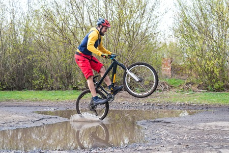 A cyclist in red shorts and a yellow jacket riding a bicycle on the rear wheel through a puddle. Active way of life in the fresh air. Standard-Bild - 121482203