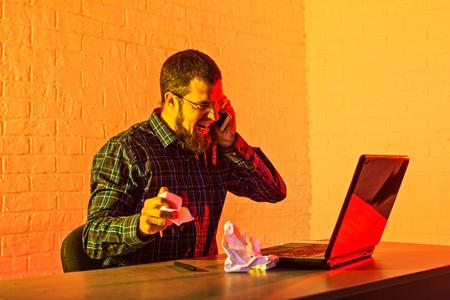 Être stressé. Homme triste en colère exprimant ses émotions tout en déchirant une feuille de papier. Homme d'affaires travaillant pour un ordinateur portable.
