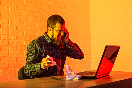 Being stressed out. Angry cheerless man expressing his emotions while tearing down a sheet of paper. Business man working for a laptop.