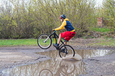 A cyclist in red shorts and a yellow jacket riding a bicycle on the rear wheel through a puddle. Active way of life in the fresh air. Standard-Bild - 121482652