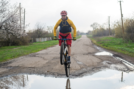 A cyclist in red shorts and a yellow jacket riding a bicycle along a street with puddles. Active way of life in the fresh air. Standard-Bild - 121482657