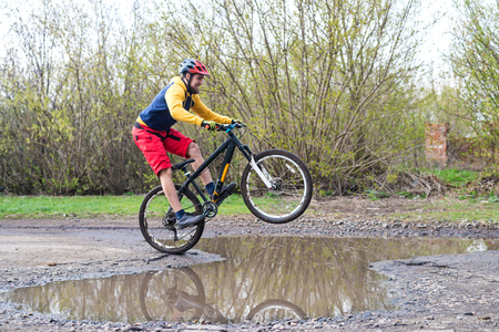 A cyclist in red shorts and a yellow jacket riding a bicycle on the rear wheel through a puddle. Active way of life in the fresh air. Standard-Bild - 121482660