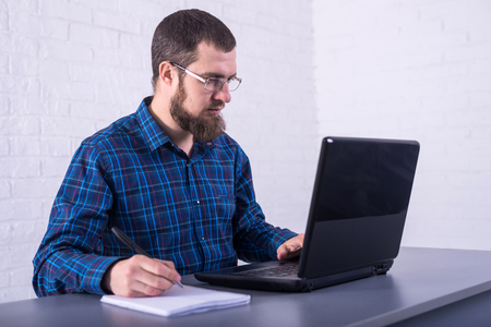 Business man with glasses working on a laptop. Freelancer fulfilling the order. Standard-Bild - 121482673