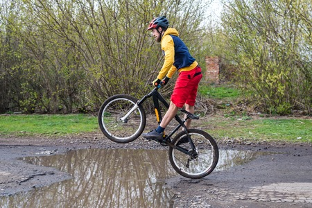 A cyclist in red shorts and a yellow jacket riding a bicycle on the rear wheel through a puddle. Active way of life in the fresh air. Standard-Bild - 121482676