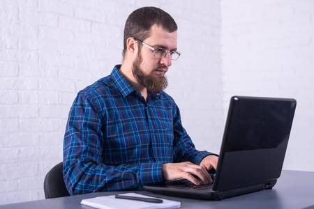 Business man with glasses working on a laptop. Freelancer fulfilling the order. Standard-Bild - 121482678