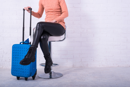 A woman with a blue suitcase is sitting on a chair, free space. Business woman at the airport, vacation. Standard-Bild - 121482680