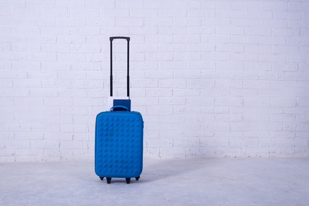 Blue suitcase near the white brick wall. Free space, travel. Standard-Bild - 121482682