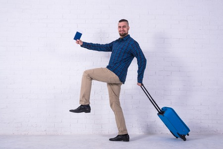 A man with a blue suitcase and a passport near a white brick wall. Vacation, free space. Standard-Bild - 121482683