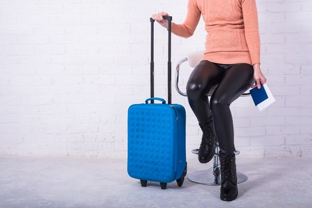 A woman with a blue suitcase is sitting on a chair, free space. Business woman at the airport, vacation. Standard-Bild - 121482684